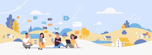 Giovani che utilizzano gadget digitali social network comunicazione uomini donne gruppo chattare online paesaggio di campagna