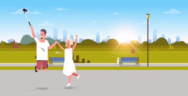 Giovani coppie che usando il bastone del selfie che prende foto sulla macchina fotografica dell'uomo dello smartphone la donna che salta divertendosi l'orizzontale integrale del fondo urbano del paesaggio dell'alba del parco della città