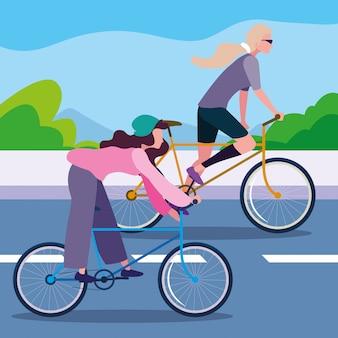 Giovani donne che guidano bici nella strada