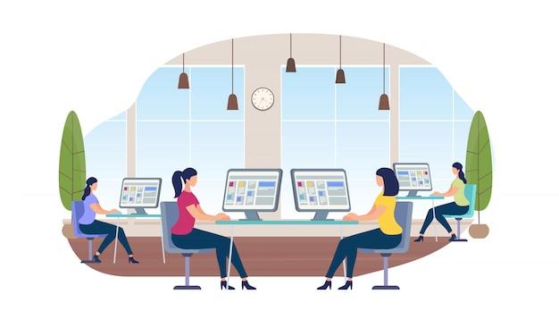 Giovani donne che lavorano su computer seduti alla scrivania