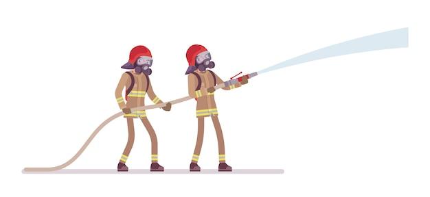 Giovani pompieri maschii con tubo flessibile dell'acqua