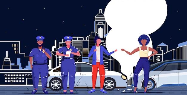 Gli agenti di polizia coppia la stesura di un rapporto scritto bene per i conducenti di razza mista che discutono vicino al paesaggio urbano danneggiato di notte di concetto di incidente d'auto delle automobili