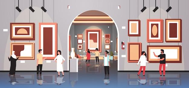 Gli spettatori dei turisti della gente nell'interno del museo della galleria di arte moderna che sembrano le opere d'arte contemporanea creativa delle pitture o le mostre orizzontali piane
