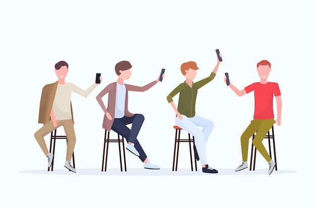 Gli uomini nelle pose differenti che prendono la foto del selfie sulla macchina fotografica dello smartphone raggruppano i personaggi dei cartoni animati maschii casuali che si siedono sulla sedia che posa il fondo bianco orizzontale integrale