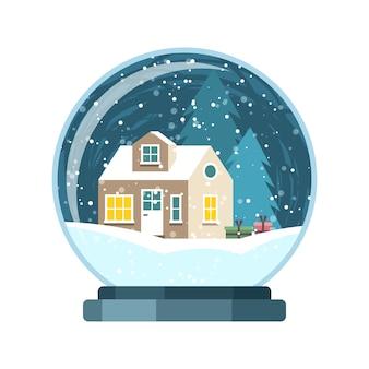 Globo della neve di natale con la casa e gli alberi