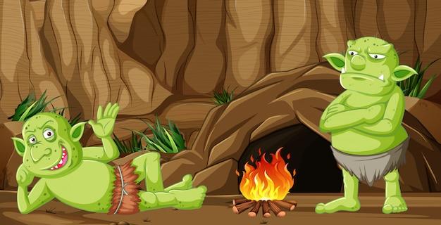 Goblin o troll con casa delle caverne e fuoco da campo in stile cartone animato