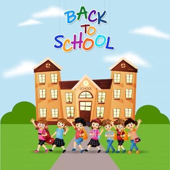 Godendo piccoli studenti di fronte all'edificio scolastico