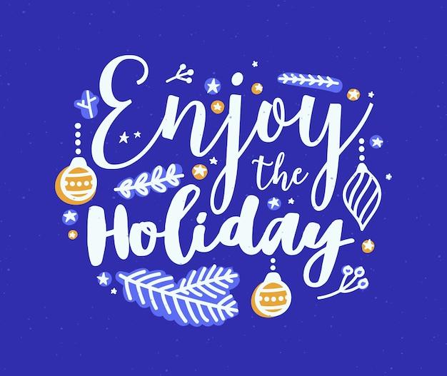 Goditi l'iscrizione the holiday scritta con caratteri calligrafici e rami di conifere decorati
