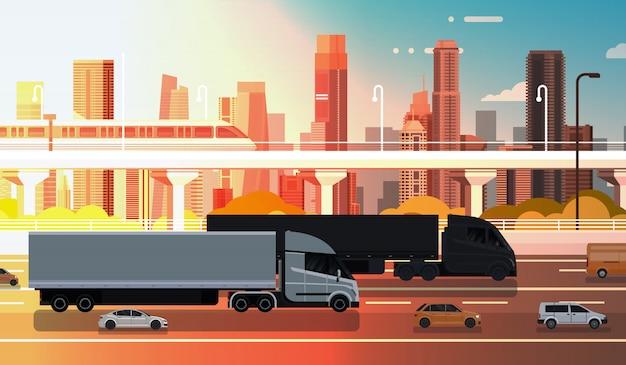 Grande camion dei semi con la strada della strada principale dei rimorchi con le automobili e il camion sopra la spedizione del paesaggio della città
