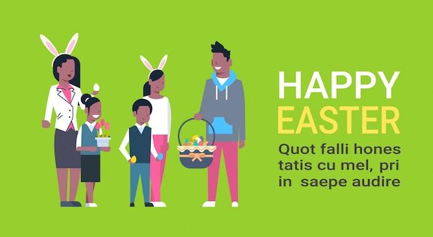 Grande famiglia afroamericana su buona pasqua. i genitori e i bambini che celebrano le vacanze di primavera indossano orecchie da coniglio