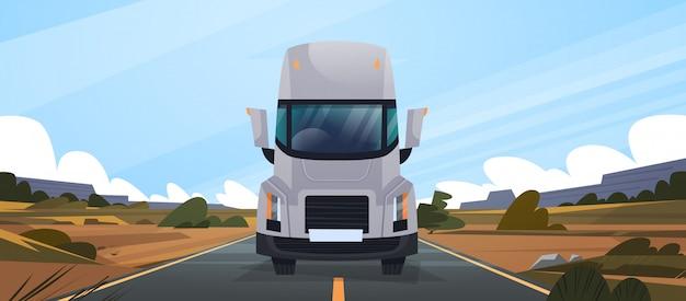 Grande rimorchio del camion che guida sulla strada in campagna front view of vahicle delivery natural landscape