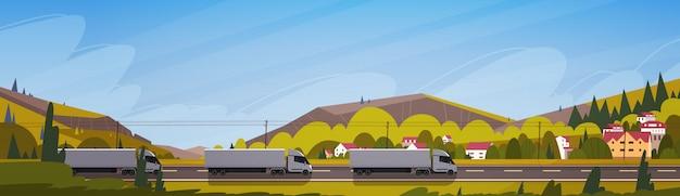Grandi rimorchi del camion dei semi che guidano strada sopra l'insegna orizzontale del paesaggio delle montagne