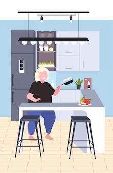 Grassa donna obesa cucinare frittelle in padella malsana nutrizione concetto di obesità sovrappeso ragazza preparazione colazione seduto al banco scrivania moderna cucina interno verticale