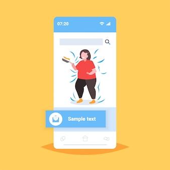 Grassa donna obesa cucinare frittelle in padella malsana nutrizione concetto di obesità sovrappeso ragazza preparazione colazione smartphone schermo applicazione mobile online