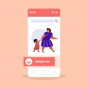Grassa madre obesa con la figlia tenendosi per mano sovrappeso donna e bambino che camminano insieme famiglia divertendosi concetto di obesità smartphone schermo online mobile app integrale