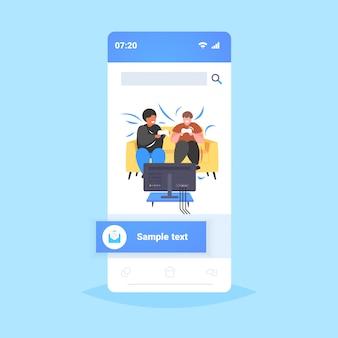 Grasso obeso uomini seduti sul divano utilizzando il joystick game pad mix gara amici coppia giocare videogiochi in tv stile di vita malsano concetto di obesità smartphone schermo online app mobile integrale