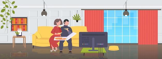 Grasso obeso uomo donna seduta sul divano a mangiare la pizza fast food malsano nutrizione concetto coppia guardare la tv sul divano moderno salotto interno a figura intera orizzontale
