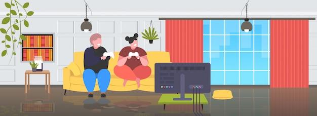 Grasso obeso uomo donna seduta sul divano utilizzando il joystick pad di gioco sovrappeso coppia esercitando videogiochi in tv obesità stile di vita malsano concetto moderno soggiorno interno a figura intera