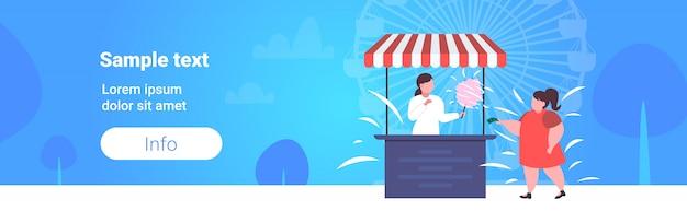Grasso ragazza obesa acquisto di gelati in stallo alimentare malsano nutrizione concetto di obesità femmina bambino divertirsi parco pubblico ruota panoramica paesaggio copia spazio