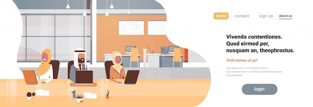 Gruppo arabo del posto di lavoro dell'ufficio facendo uso dell'insegna di processo di lavoro del computer portatile
