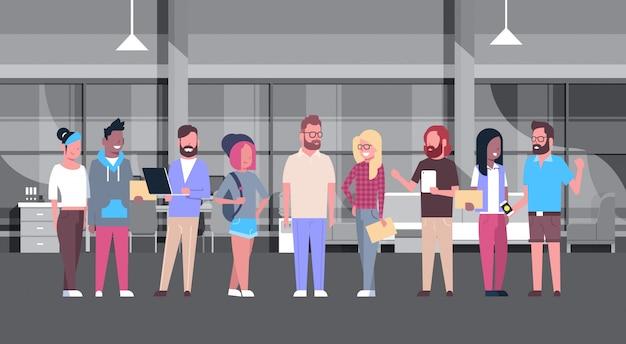 Gruppo casuale della gente dell'ufficio di coworking che lavora insieme nel centro moderno del collega
