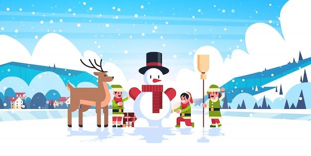 Gruppo degli elfi verdi che fa l'illustrazione di buon natale del pupazzo di neve