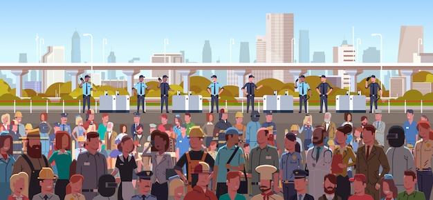 Gruppo di agenti di polizia di razza mista controllo diverse occupazioni folla di persone in protesta dimostrazione sciopero festa del lavoro città paesaggio urbano