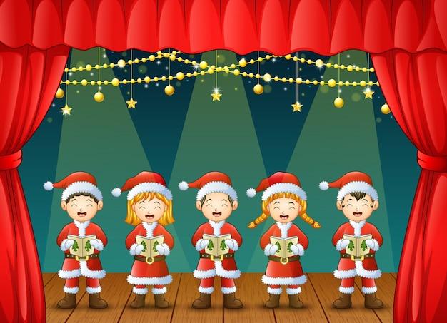 Gruppo di bambini che cantano canti di natale sul palco