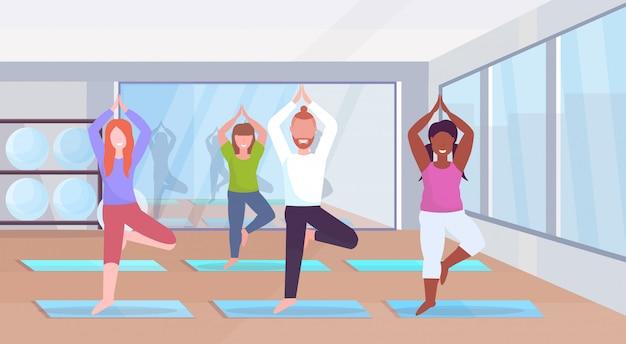Gruppo di donne sportive uomo facendo esercizi di yoga mescolano persone di razza gara meditando in piedi nella posizione dell'albero che risolve il concetto di stile di vita sano moderno palestra studio interno integrale