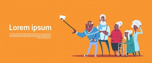 Gruppo di gente senior che prende la foto di selfie con il nonno e la nonna afroamericani moderni del bastone di auto