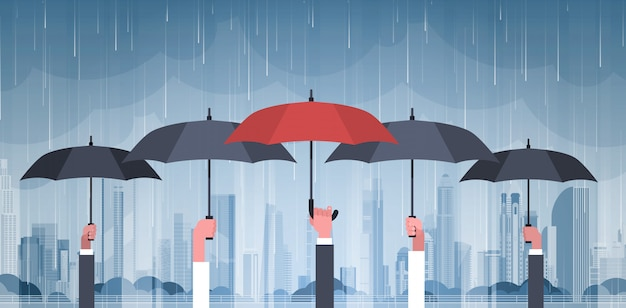 Gruppo di mani che tengono gli ombrelli sopra la tempesta nel ciclone enorme di uragano del fondo della pioggia della città nel concetto naturale di disastro della città