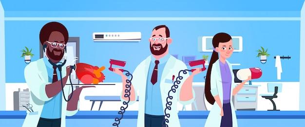 Gruppo di medici che tengono attrezzatura per rianimazione cardiaca