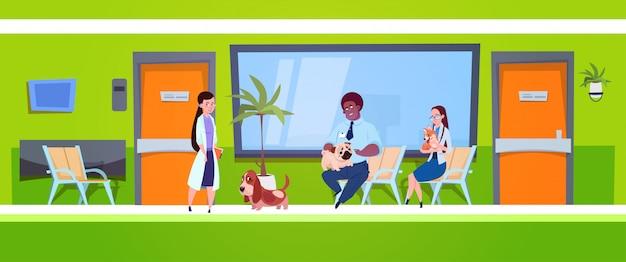 Gruppo di persone con i cani che si siedono nella sala di attesa nel concetto della medicina veterinaria della clinica del veterinario