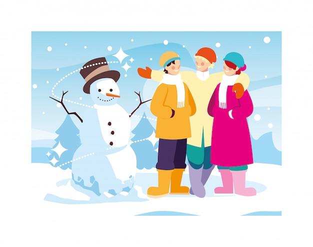 Gruppo di persone con pupazzo di neve nel paesaggio invernale