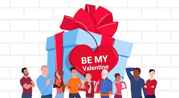 Gruppo di persone dell'insegna di giorno di biglietti di s. valentino sopra il grande contenitore di regalo con l'etichetta a forma di cuore