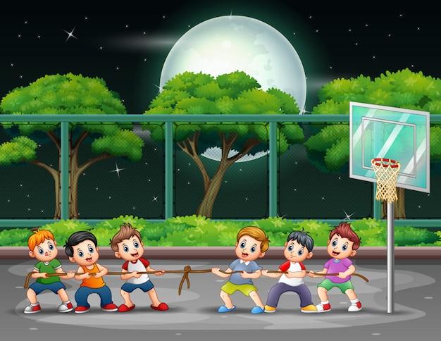 Gruppo di ragazzi che giocano alla fune sul campo di notte
