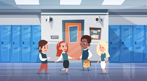 Gruppo di scolari negli allievi della corsa della miscela del corridoio del banco sopra la fila degli armadietti
