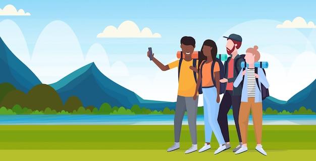 Gruppo di turisti escursionisti con zaini prendendo selfie foto su smartphone fotocamera escursioni concetto mix corsa viaggiatori su escursione fiume montagne paesaggio sfondo piatto orizzontale a figura intera