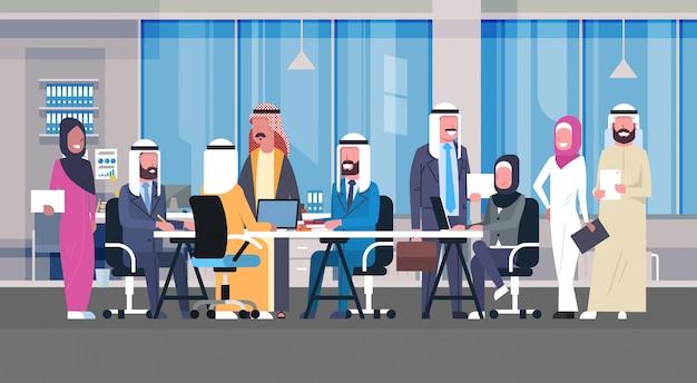 Gruppo di uomini d'affari arabi che lavorano insieme in ufficio sit at desk team di lavoratori musulmani riunione di brainstorming