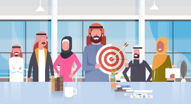 Gruppo di uomini d'affari arabi in ufficio moderno uomo d'affari hold target aim squadra musulmana indossando abiti tradizionali