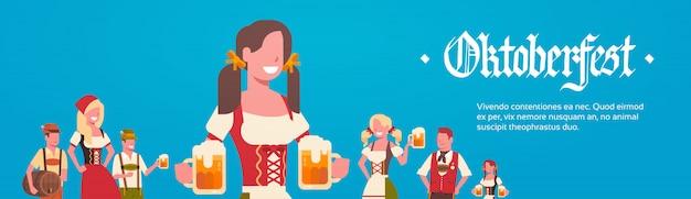 Gruppo di uomo e donna che indossano i camerieri di vestiti tradizionali tedeschi che tengono concetto del partito di oktoberfest delle tazze di birra