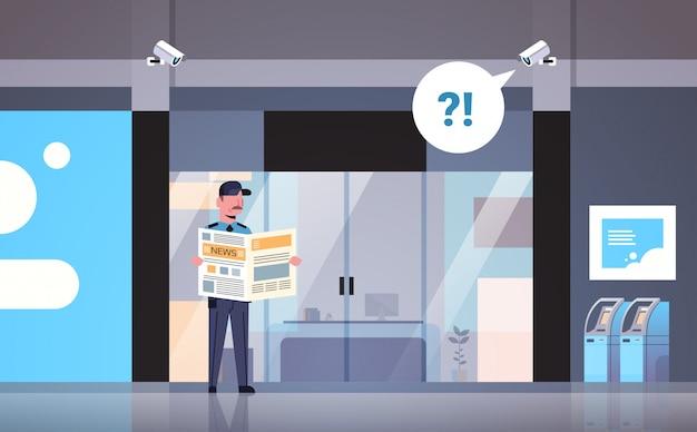 Guardia di sicurezza uomo leggendo il giornale distratto sul posto di lavoro