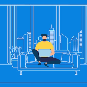 Guy barbuto che lavora al computer portatile su fondo blu