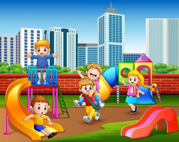 Happy bambini dell'asilo che giocano nel parco giochi