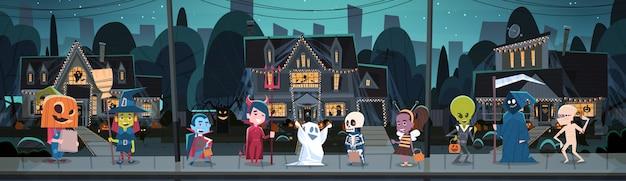 I bambini che portano i costumi dei mostri che camminano in città inganna o scherza il concetto felice di festa dell'insegna di halloween