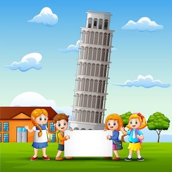 I bambini del fumetto portano una lavagna davanti al fondo della torre di pisa