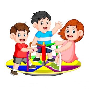 I bambini giocano alla giostra con piacere