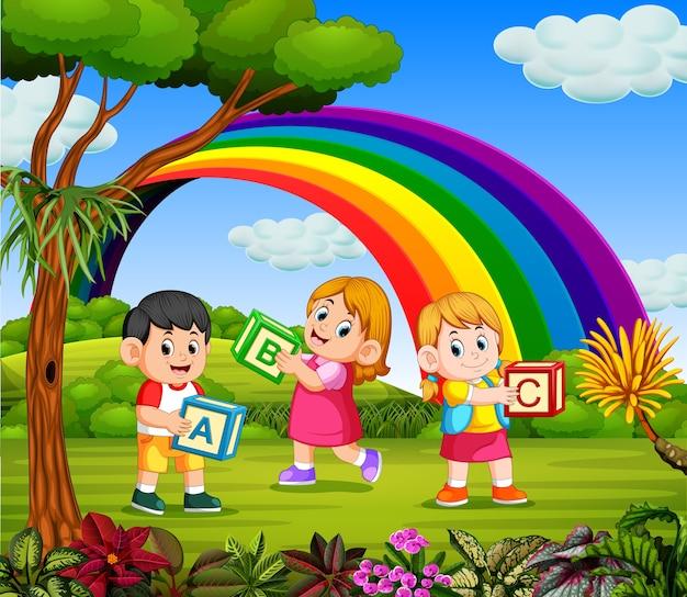 I bambini giocano e tengono la loro scatola di alfabeto