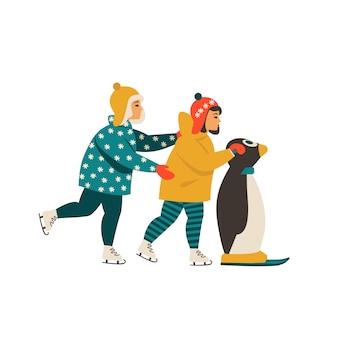 I bambini imparano a pattinare sul ghiaccio mentre si aggrappano al pinguino.