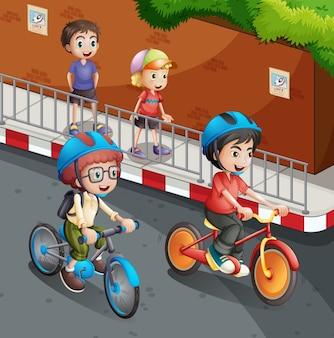 I bambini in sella alla bicicletta sulla strada con il casco